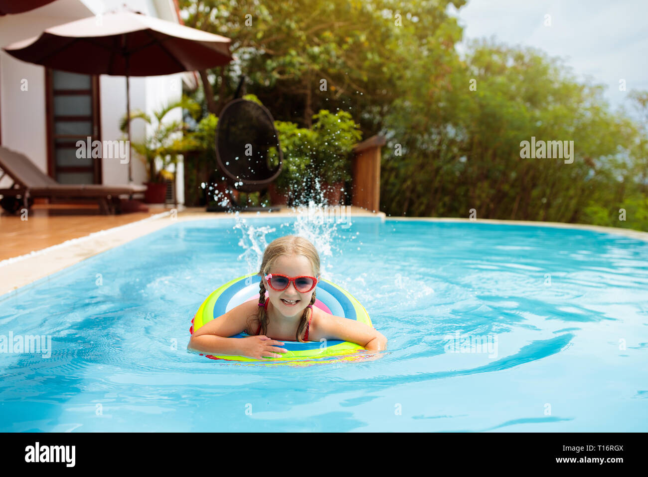 180d22d81d Child with goggles in swimming pool. Little girl learning to swim and dive  in outdoor pool of tropical resort. Swimming with kids. Healthy sport activ