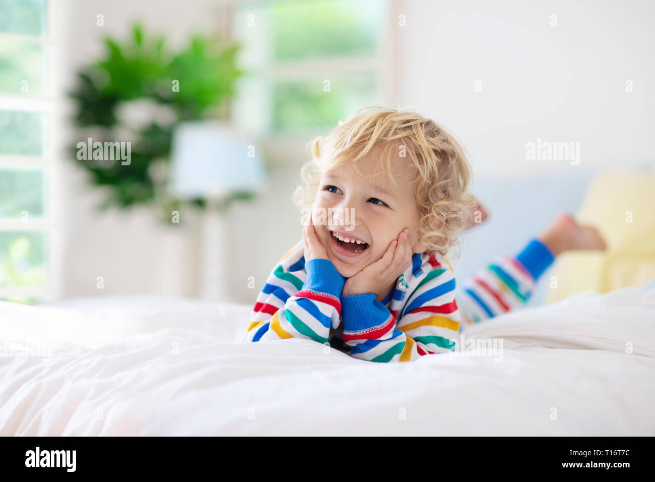 Child playing in bed in white sunny bedroom with window kids room and interior design