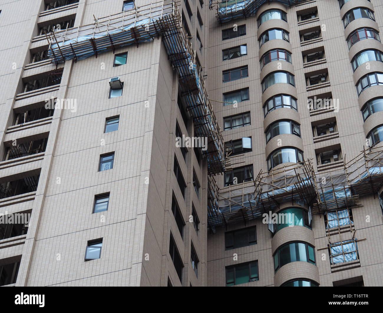 Central, Hong Kong - 1 November 2017: scaffolding of bamboo provide a platform for high-altitude maintenance work at several apartments. - Stock Image
