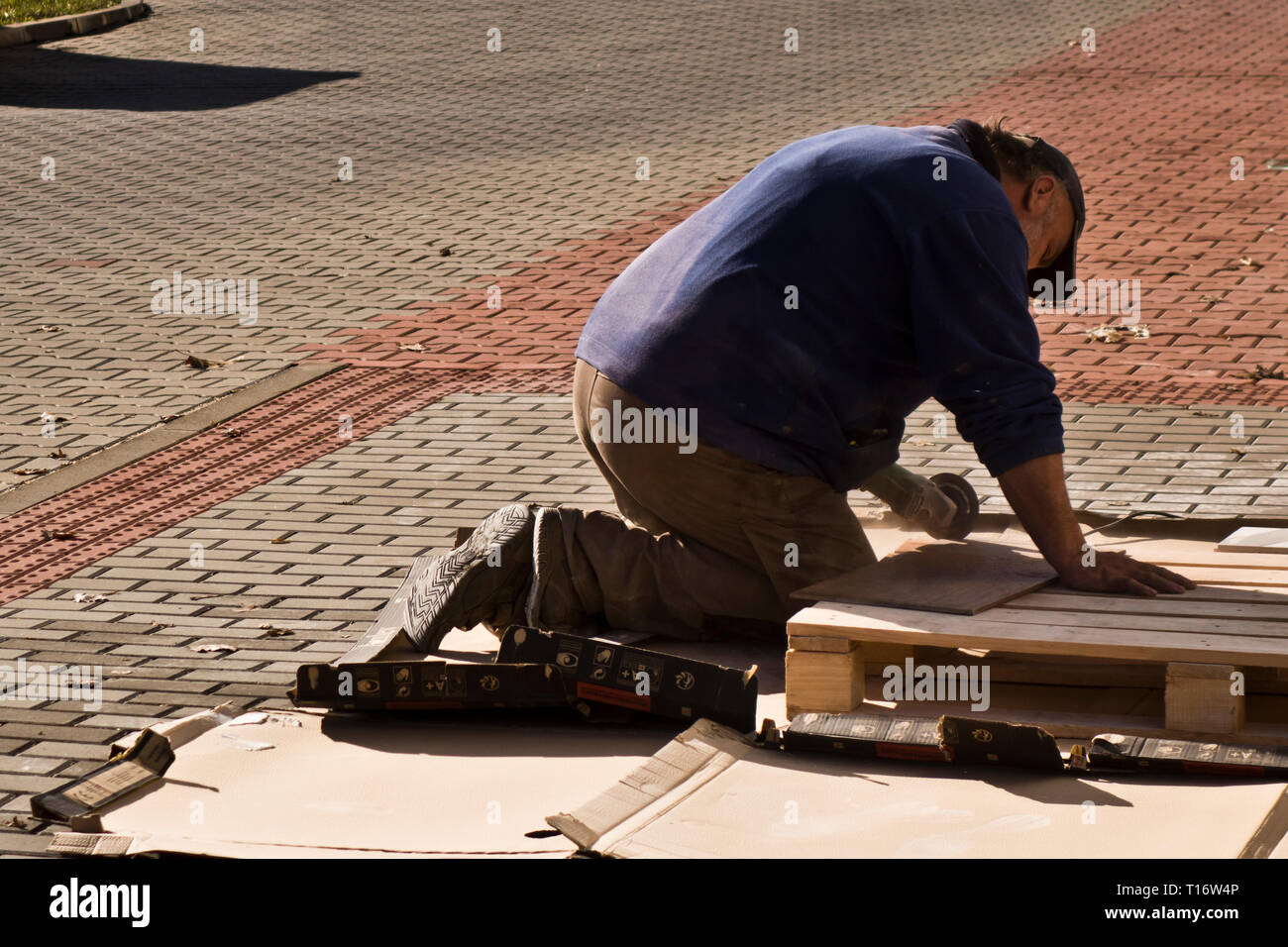 worker cutting a slab of marble using a saw with diamond blade - Stock Image