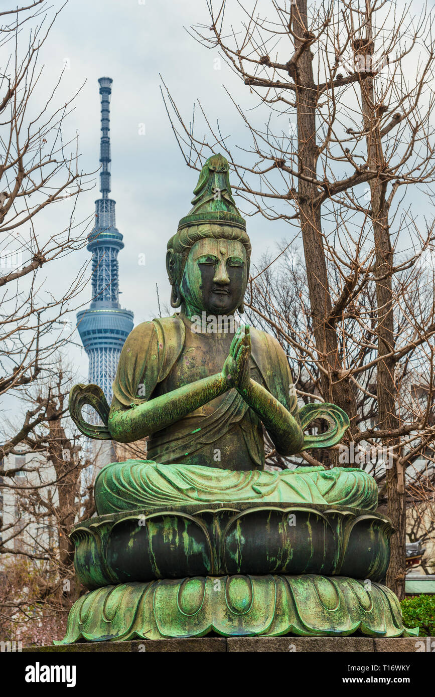 Japan between tradition and modernity. Praying Buddha old statue near Asakusa Temple with new Tokyo Skytree in the background - Stock Image