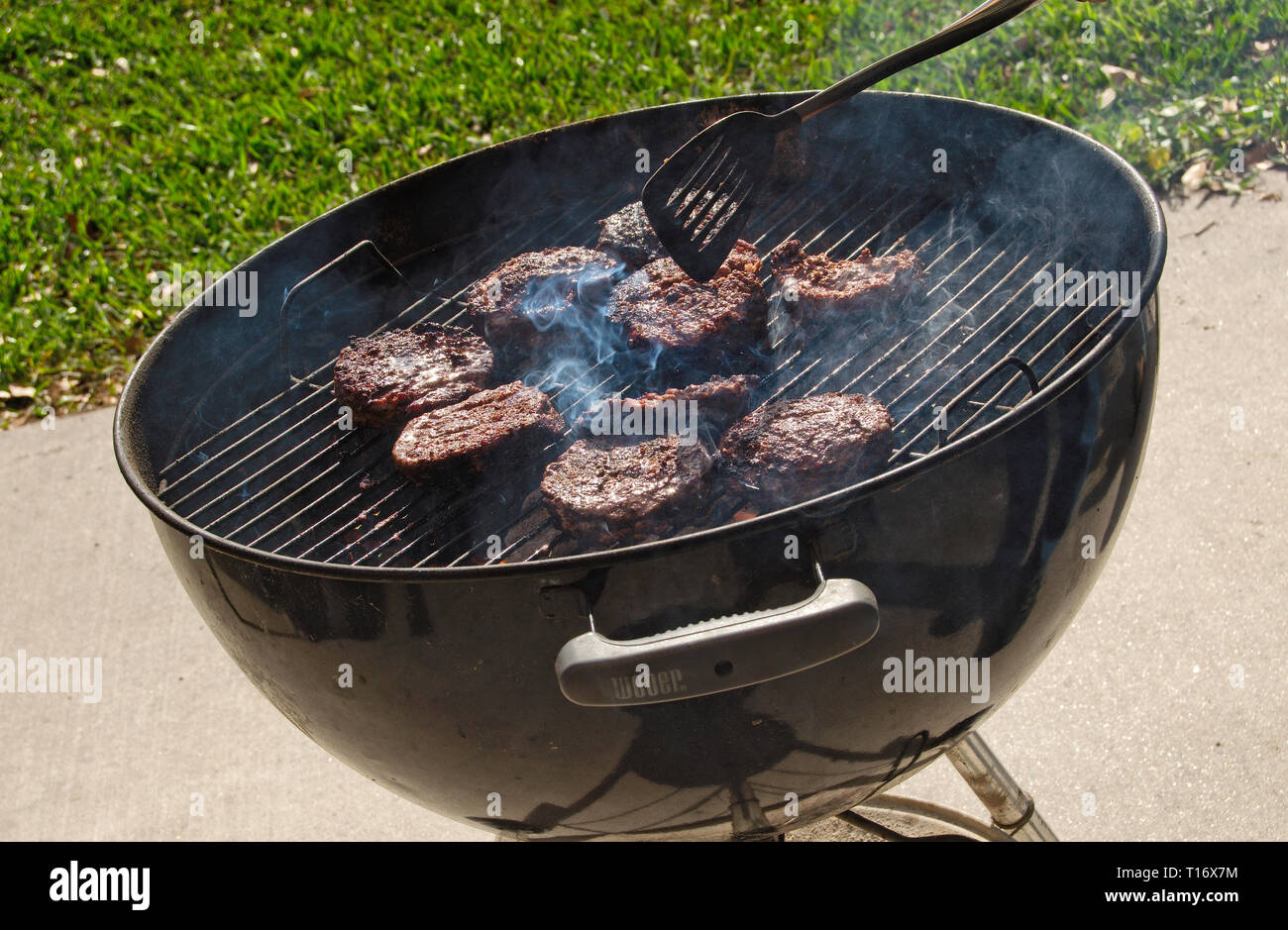 Man cooking hamburger patties on black grill - Stock Image