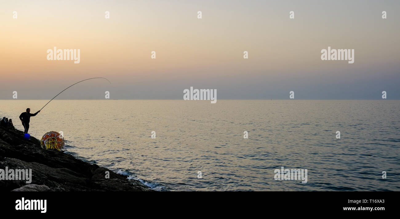 December 29, 2018 - Abu Dhabi, UAE: Silhouette of a man fishing with a fishing rod at evening - Stock Image