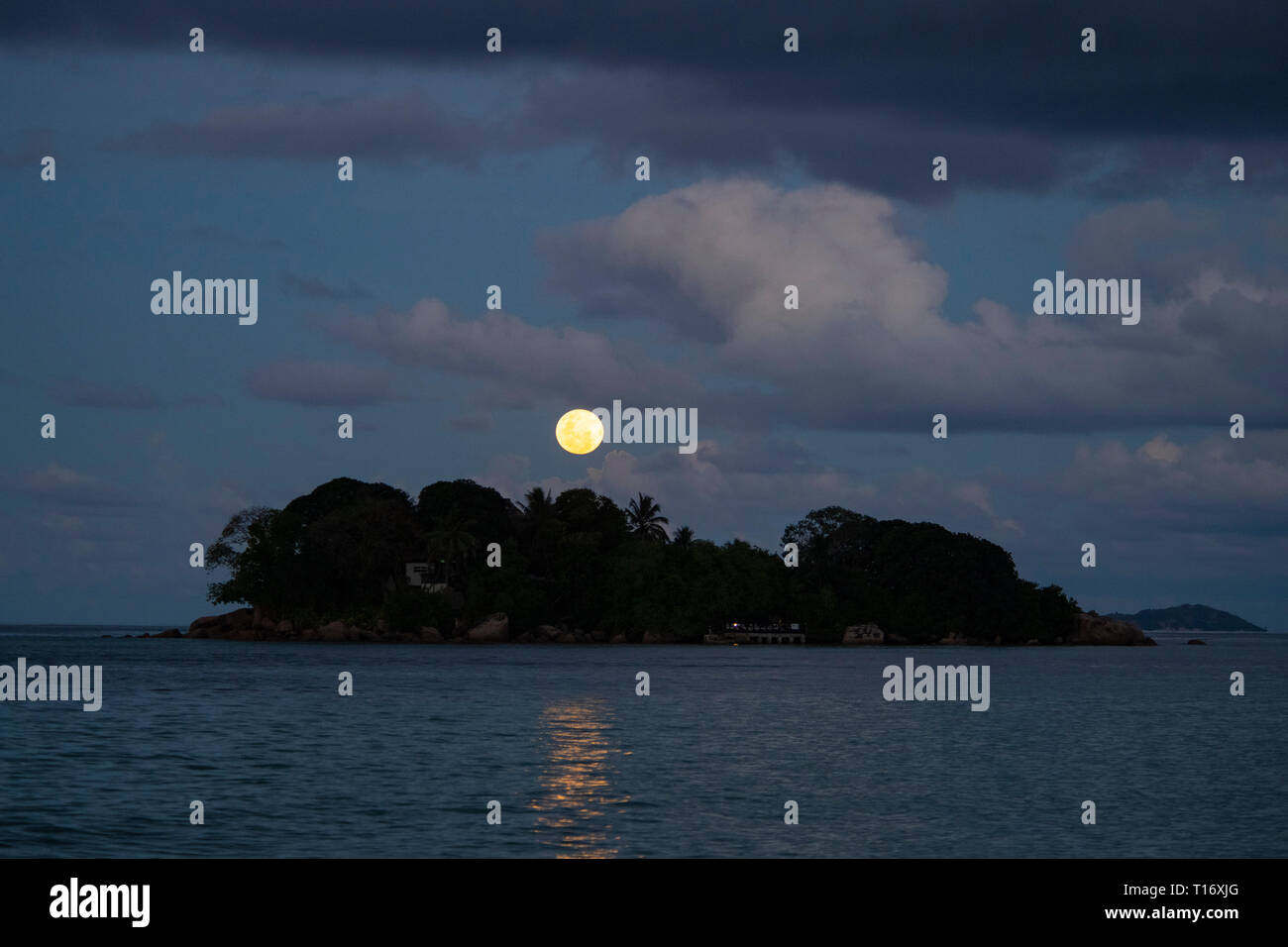 A full moon rising over Chauve Souris island off Praslin, the Seychelles Stock Photo