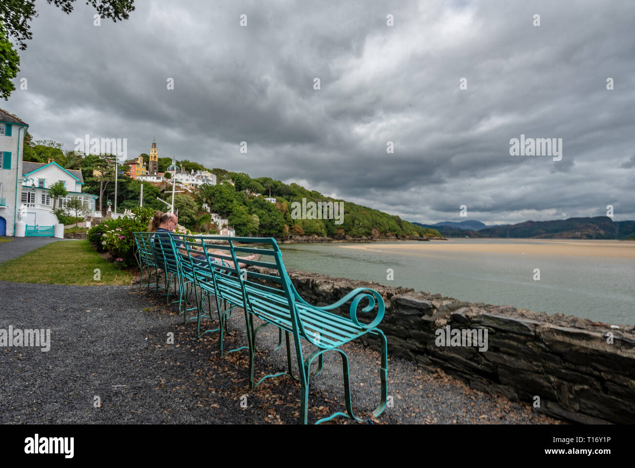 Couple relaxing on a long turquoise iron bench by the seashore, Portmeirion, Gwynedd, North Wales, United Kingdom - Stock Image