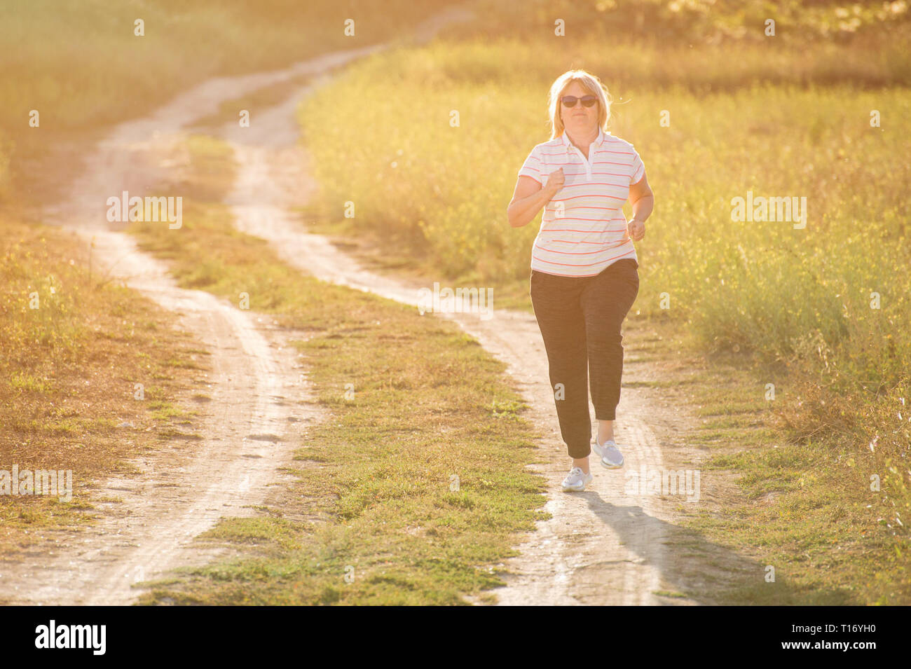 active fat adult woman running along track outdoor leisure workout - Stock Image
