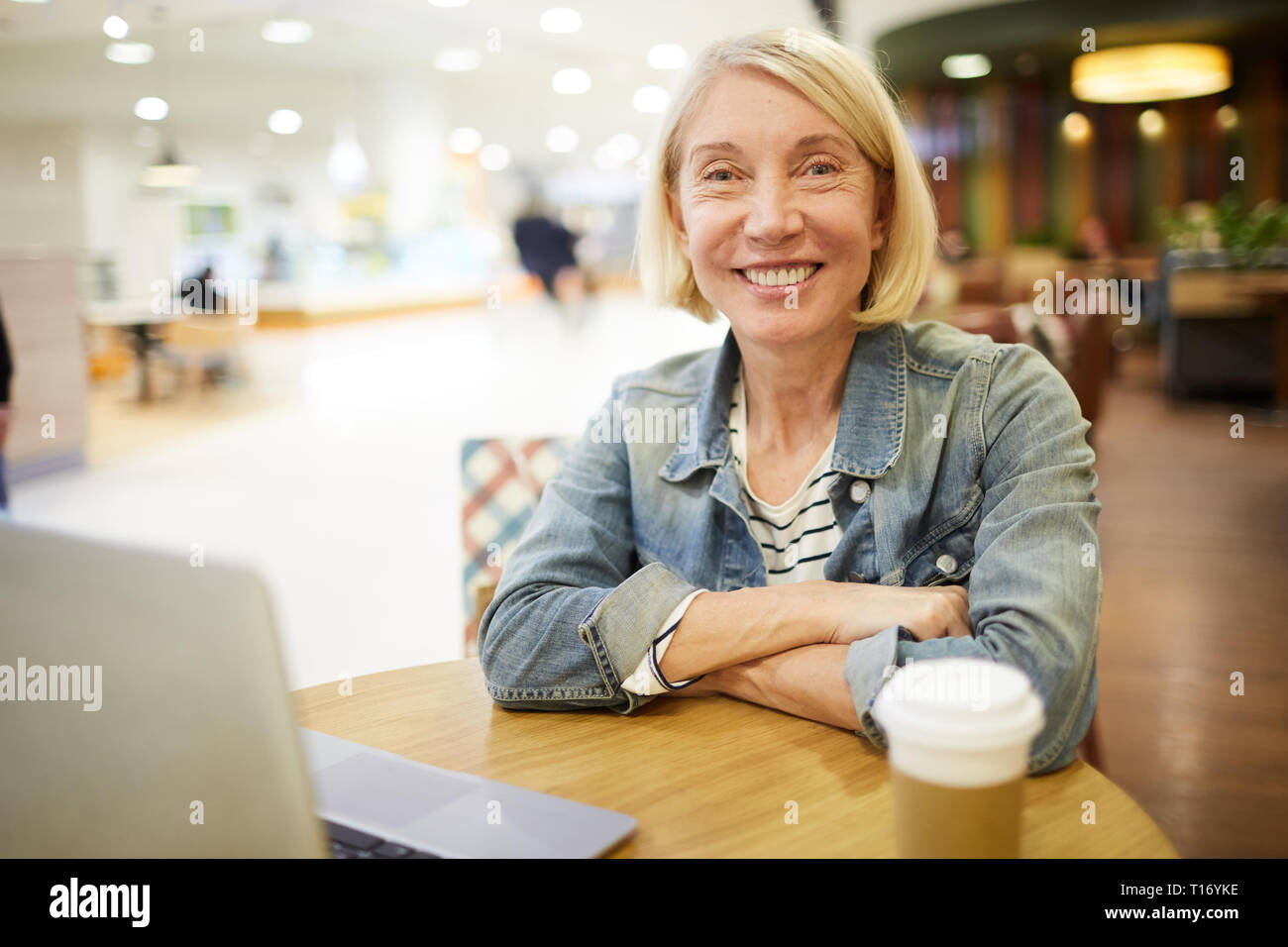 Cheerful freelance woman working in cafe - Stock Image