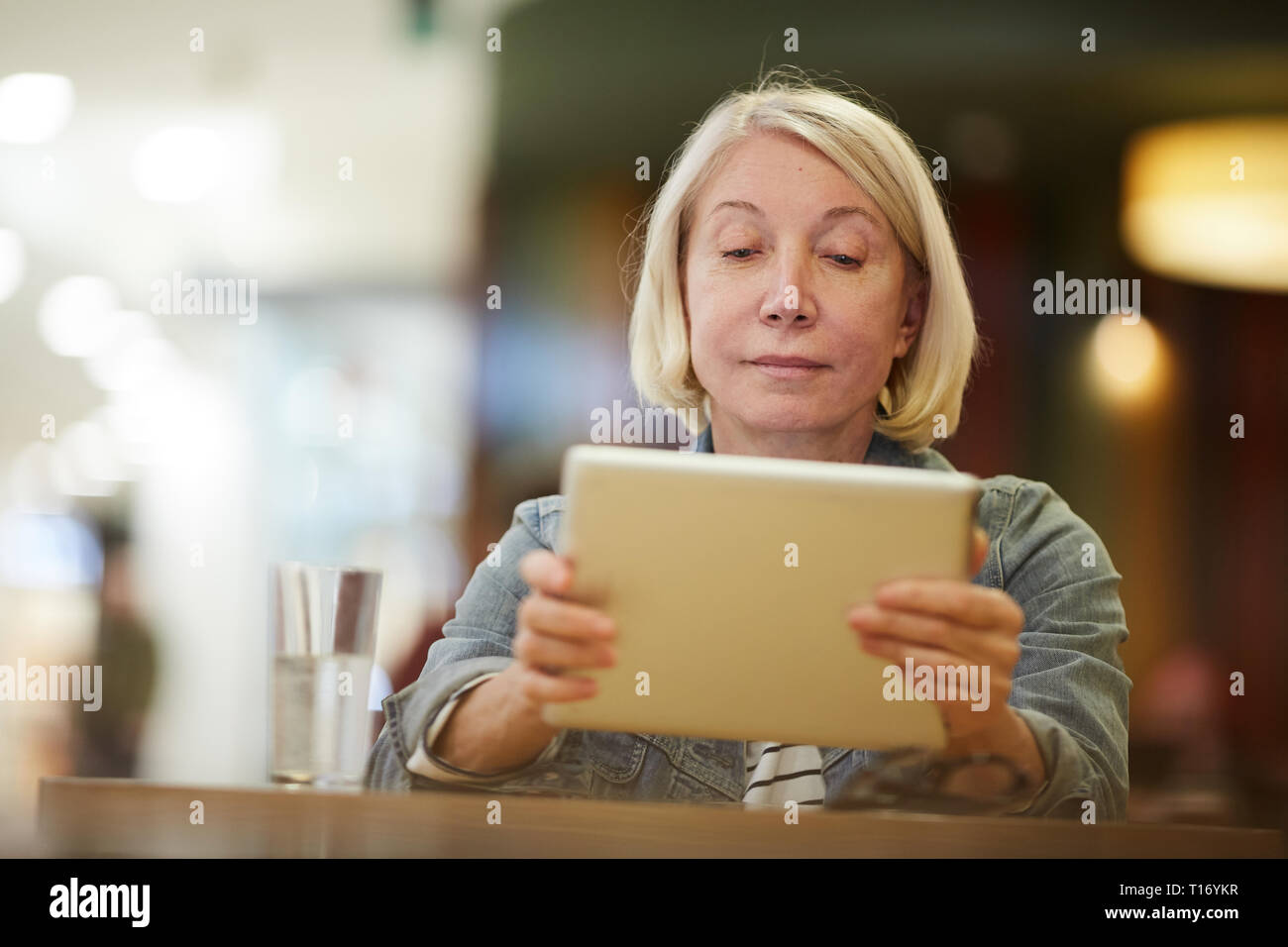 Pensive lady watching video on tablet - Stock Image