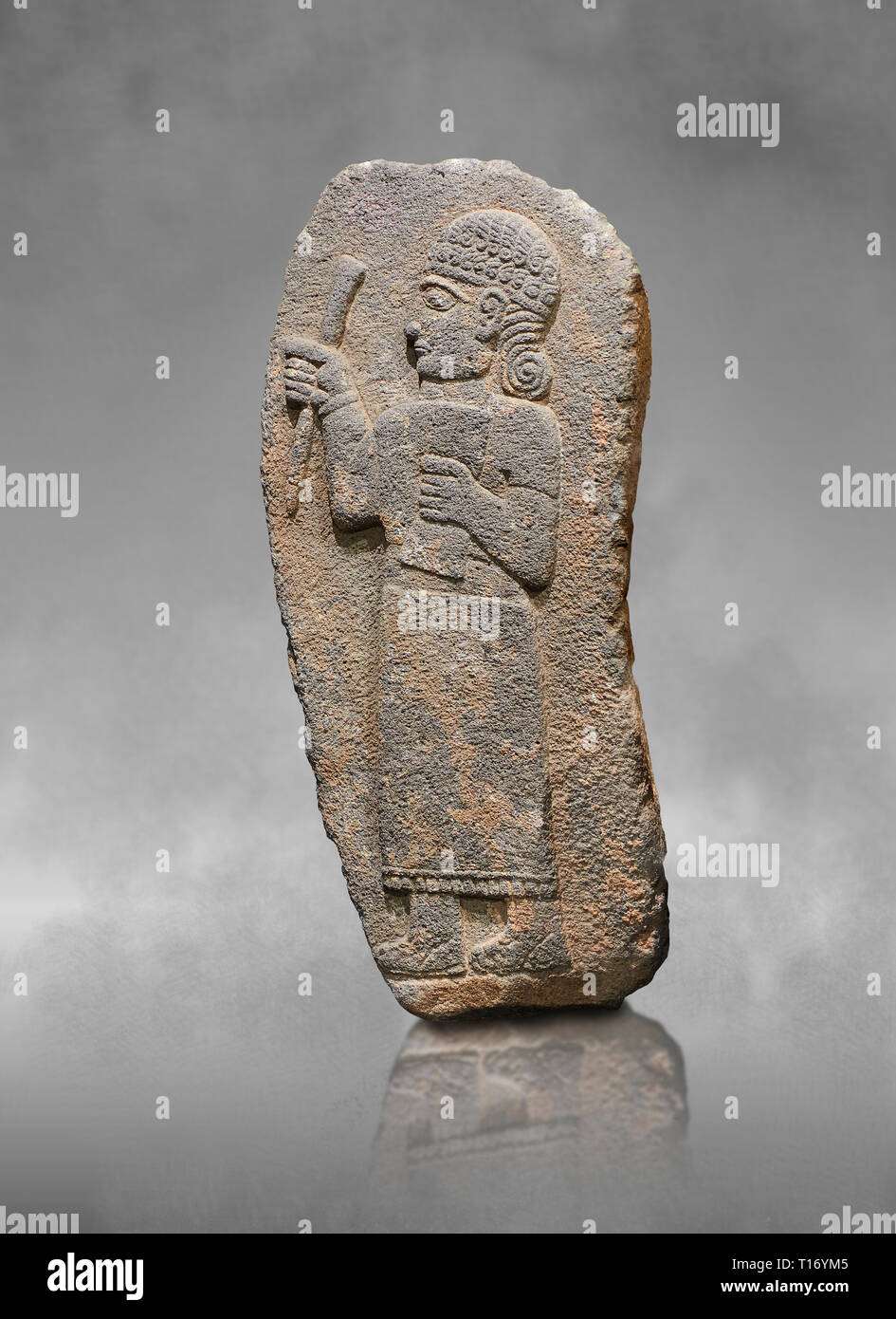Hittite monumental relief sculpture of a figure holding a document. Adana Archaeology Museum, Turkey. Against a grey art background Stock Photo