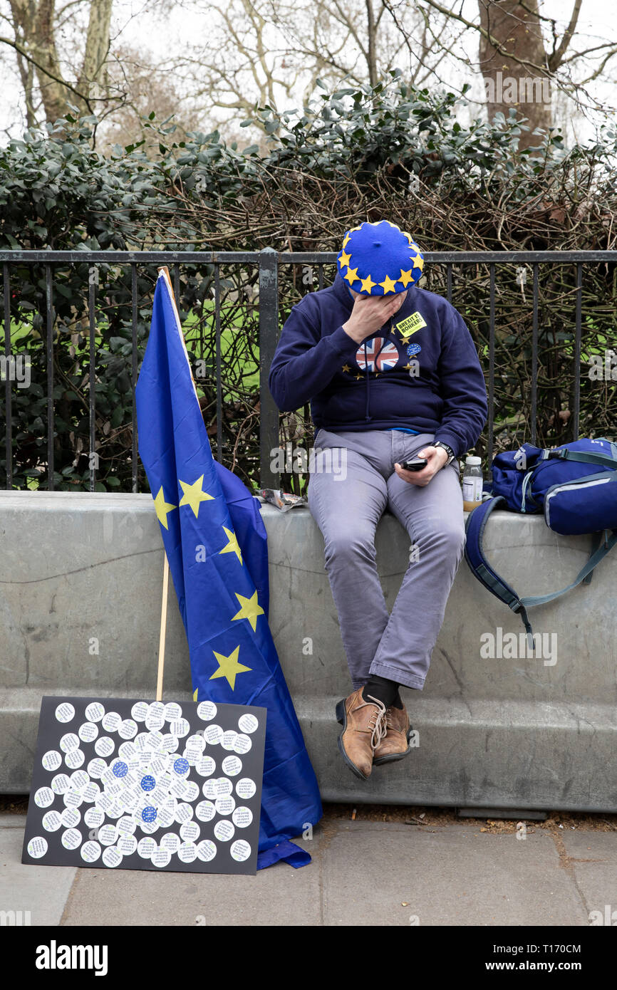 Man with EU flag and beret sat on wall looking at phone, People's Vote March, London, England Stock Photo