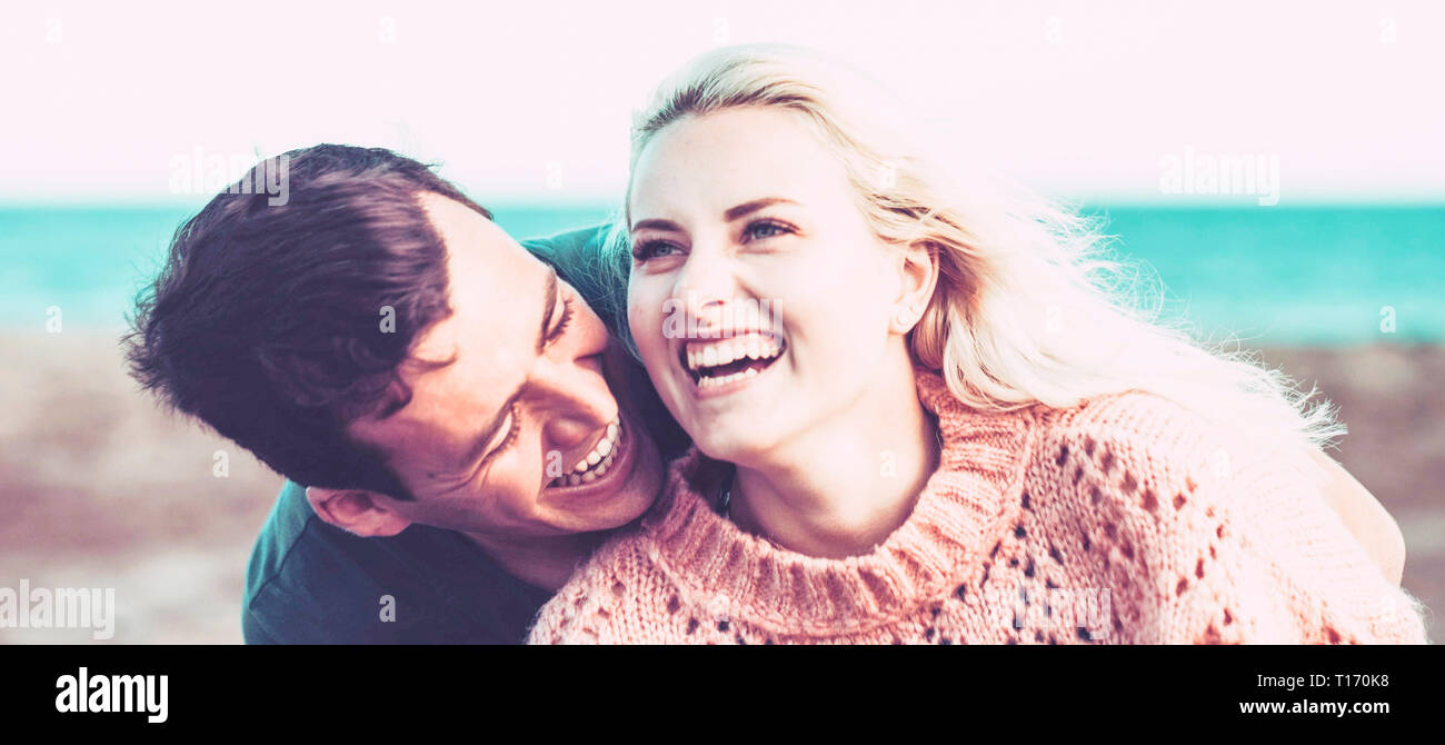 young caucasian couple blonde and black hair stay together with joy and love outdoor with beach and ocean in background. leisure vacation concept with - Stock Image