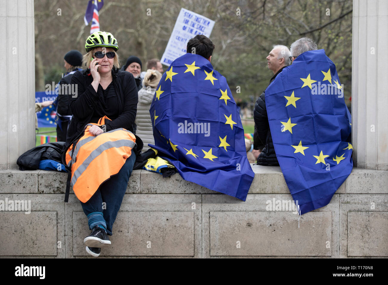 Woman on phone and two people wrapped in European Union flags sat on wall, People's Vote March, London, England - Stock Image