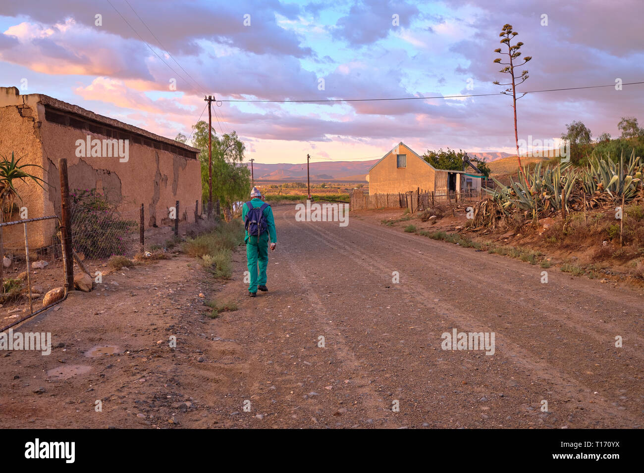 Karoo dirt road leading to a bend in morning light. Man in green overall by farm house seen from back walking to work Stock Photo