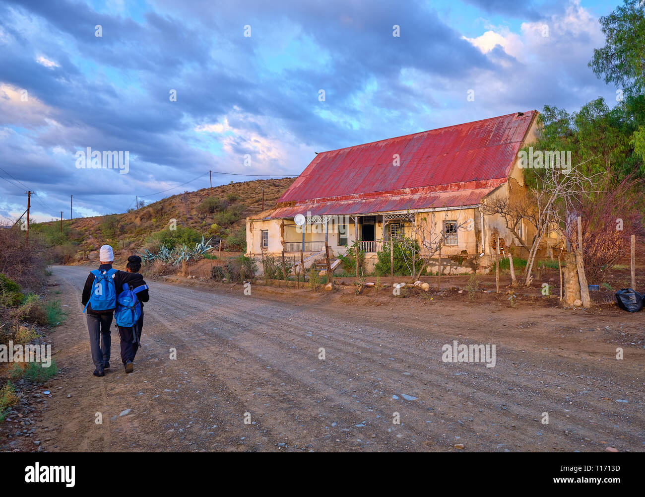 Karoo dirt road leading to a bend in morning light. Two teenagers  seen from back walking to school, passing ancient farm house Stock Photo