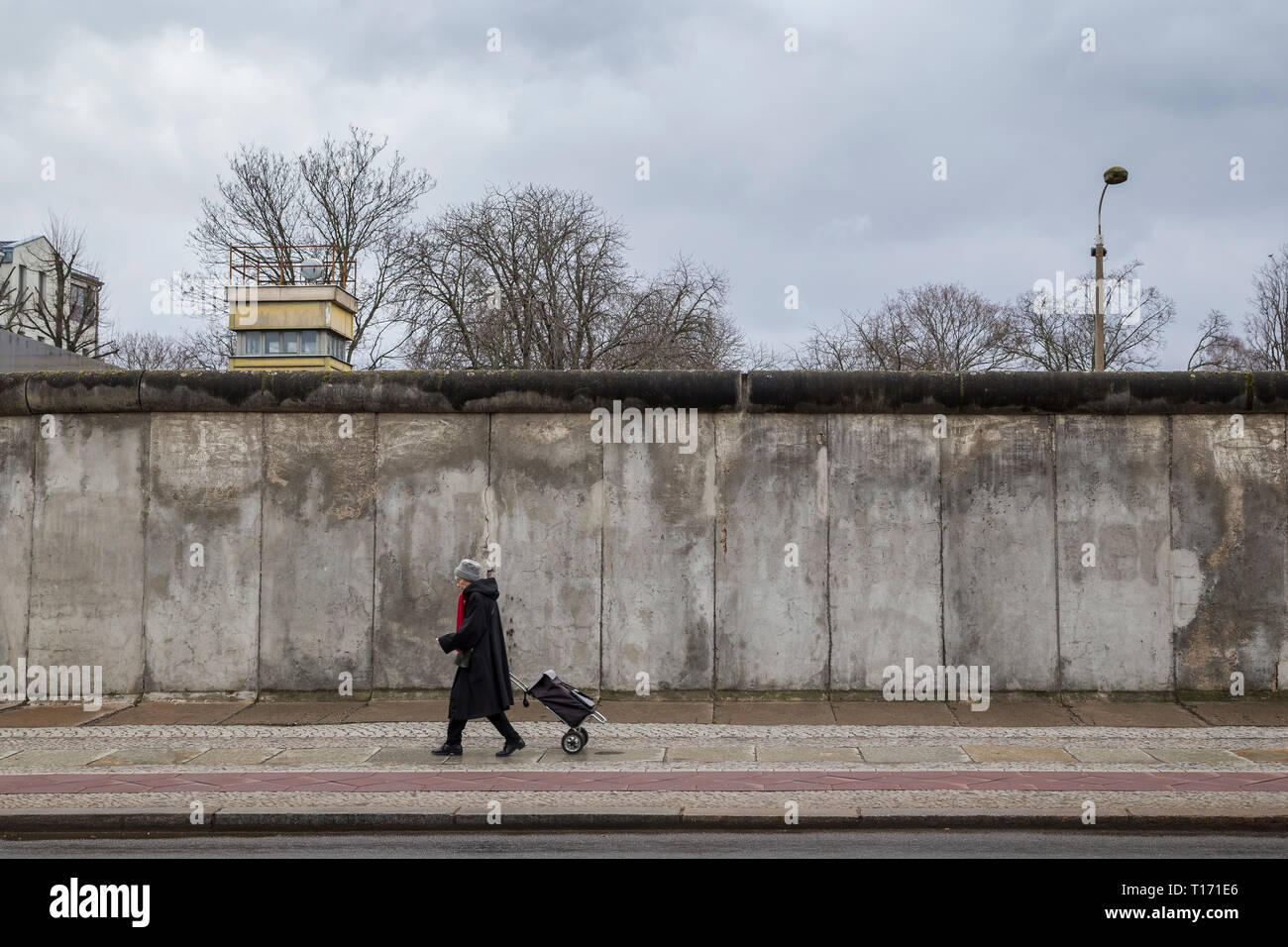 Old woman walking in front view of the original Berlin Wall and watchtower at the Berlin Wall Memorial (Berliner Mauer) in Berlin, Germany. - Stock Image
