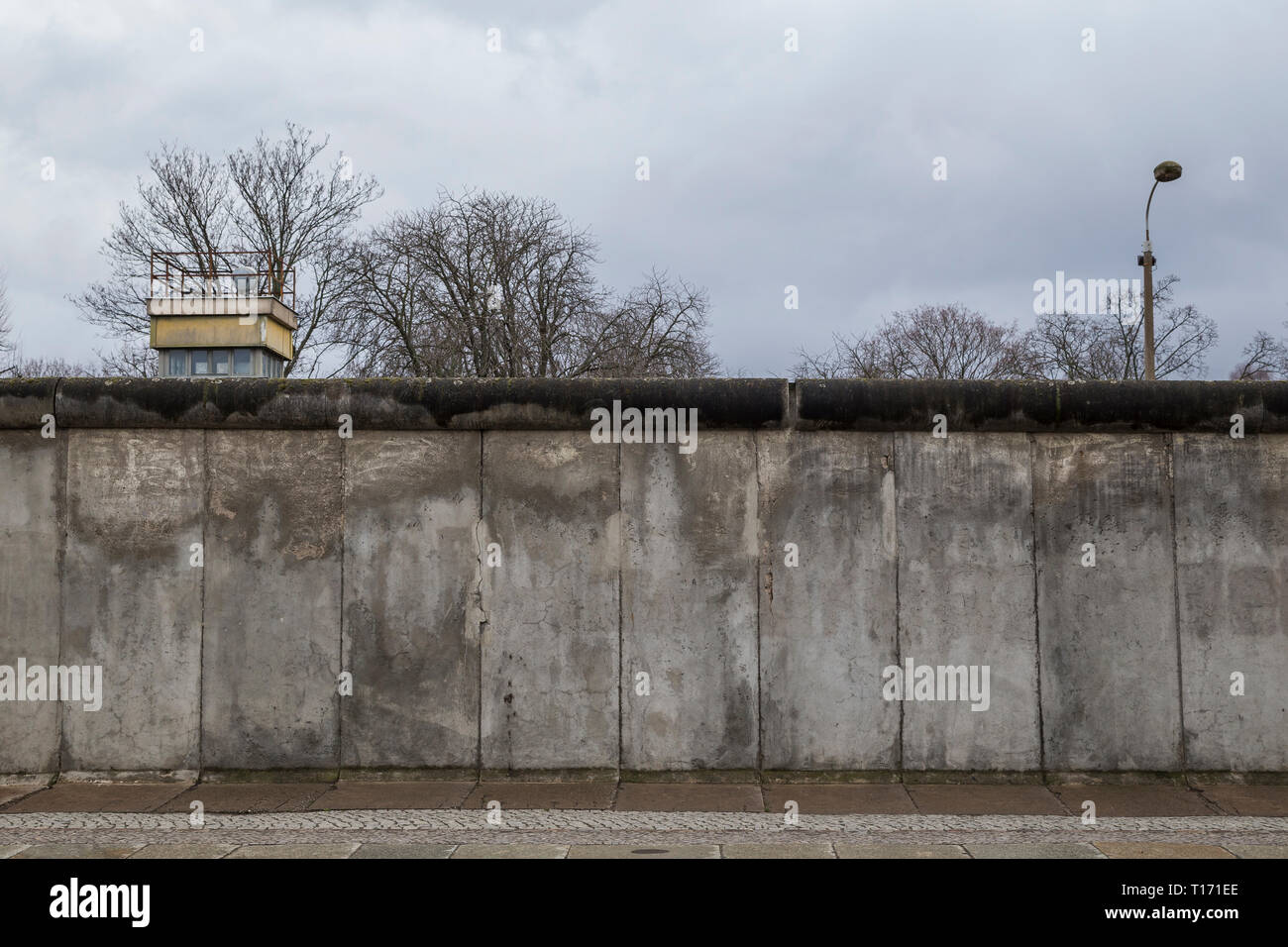 Front view of a section of the original Berlin Wall and watchtower at the Berlin Wall Memorial (Berliner Mauer) in Berlin, Germany, on a cloudy day. - Stock Image