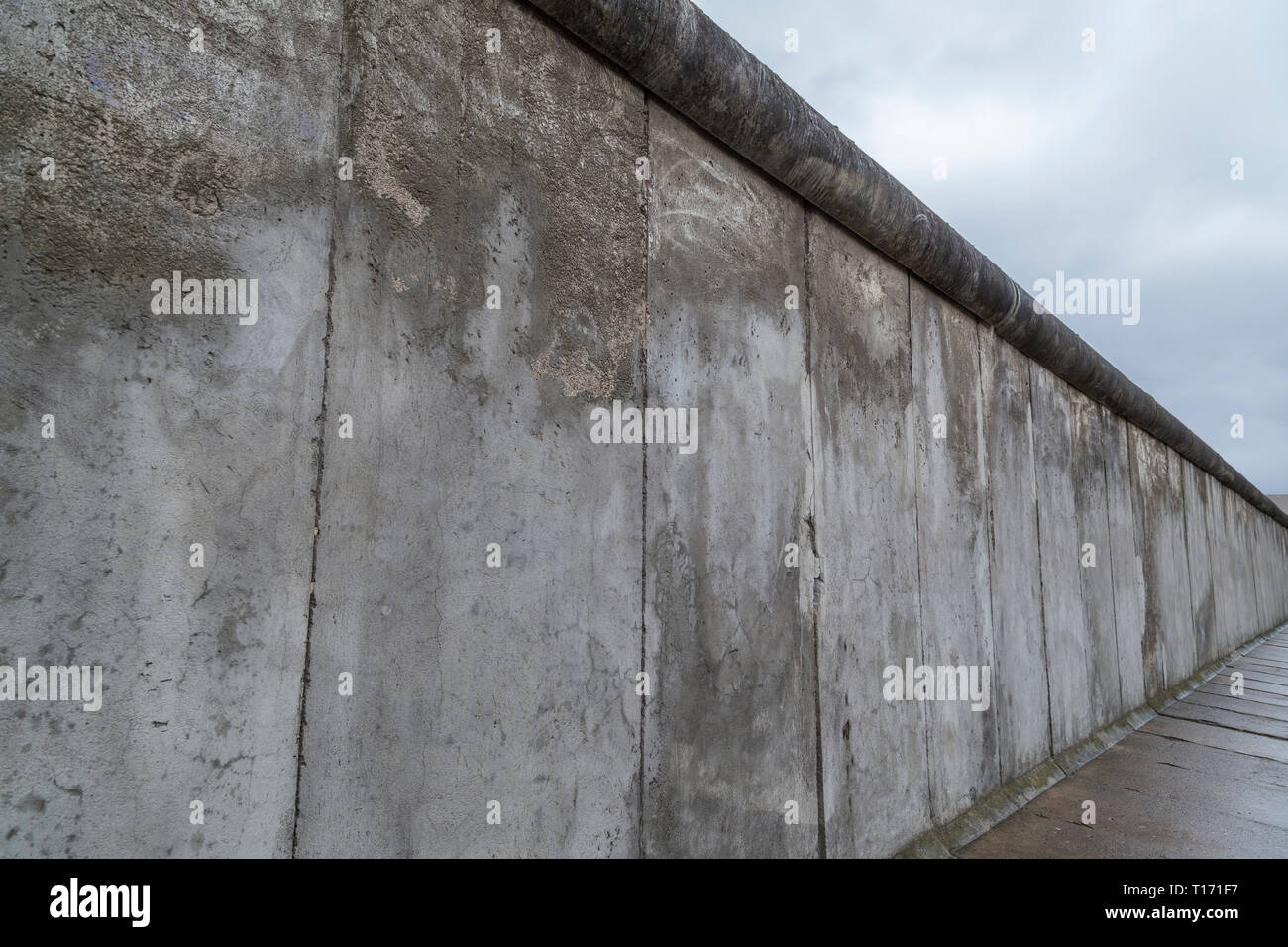 Side view of a section of the original Berlin Wall at the Berlin Wall Memorial (Berliner Mauer) in Berlin, Germany, on a cloudy day. Stock Photo