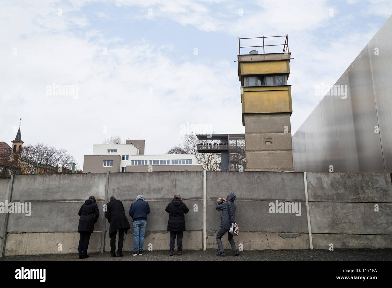 People at the Berlin Wall Memorial (Berliner Mauer) in Berlin, Germany. Watchtower is behind the Berlin Wall. Documentation Center is in the backgroun - Stock Image