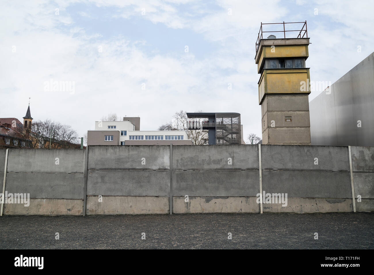 Berlin Wall and watchtower at the Berlin Wall Memorial (Berliner Mauer) in Berlin, Germany. Documentation Center and viewing platform in background. - Stock Image