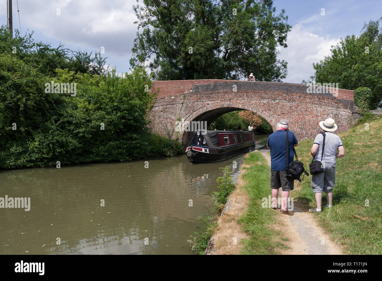 Three seniors, members of a U3A photography group, taking photos of a narrowboat on the canal at Blisworth, Northamptonshire, UK - Stock Image
