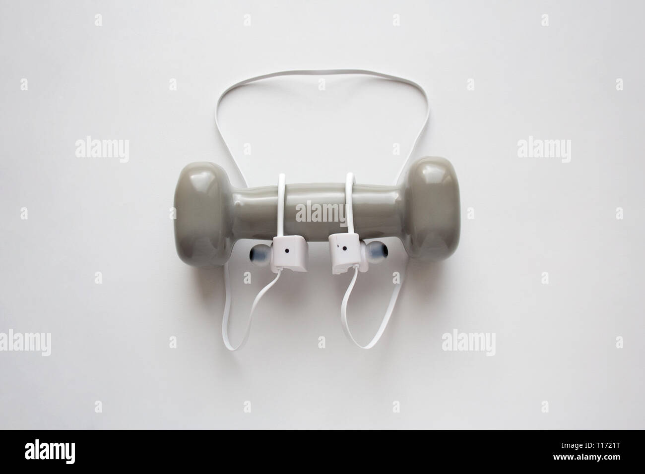 White sport wireless earbuds with grey dumbbell isolated on white background - Stock Image