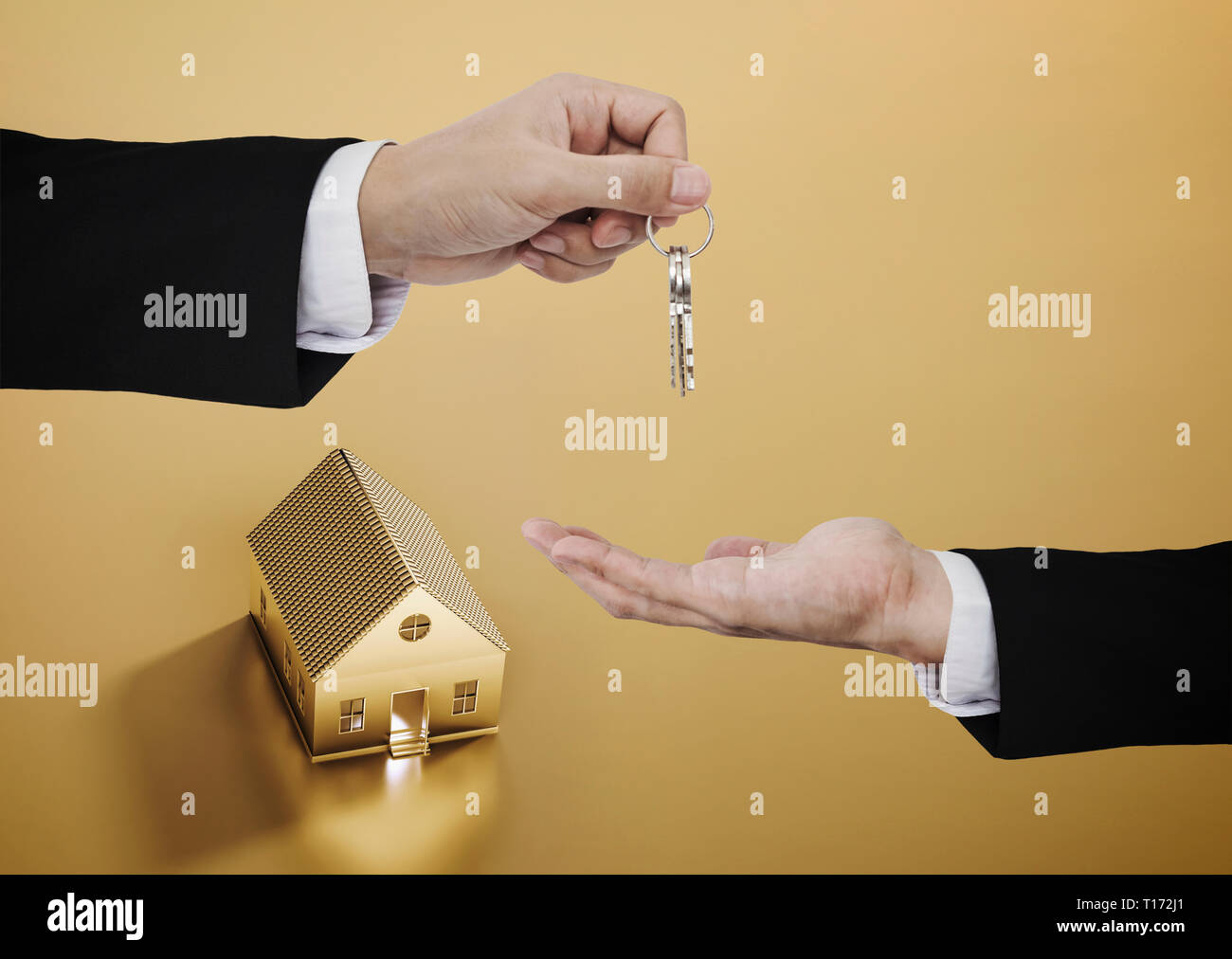 Real estate business, residential rental and investment. Businessman handover key with golden house background Stock Photo
