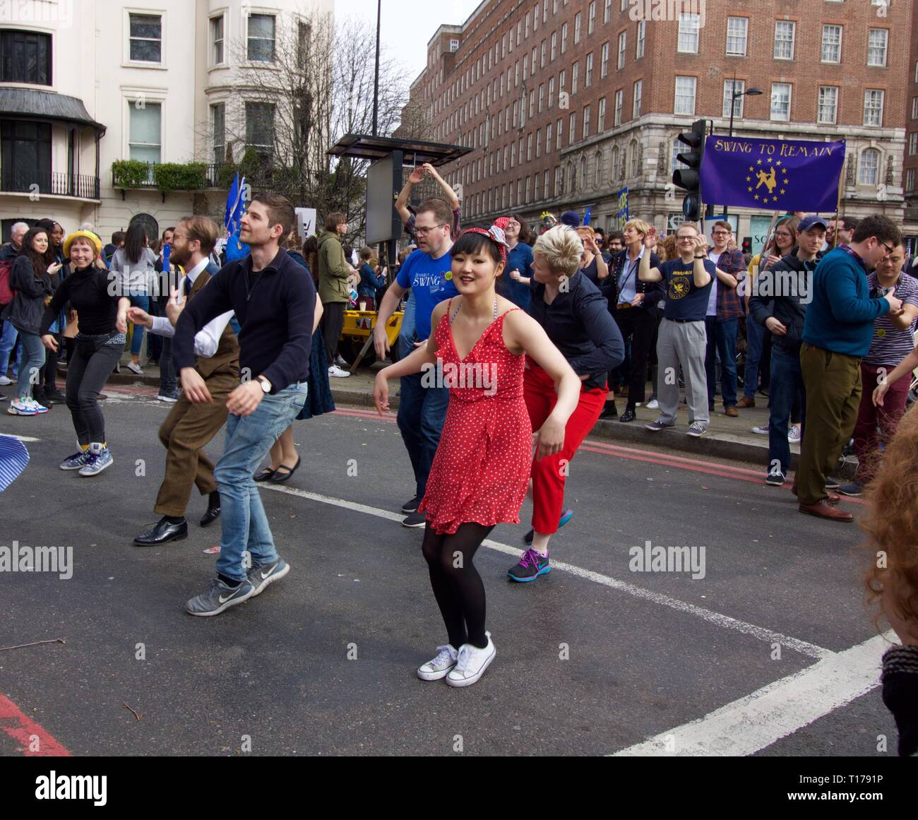 Girl dancing in the street at Swing for Remain during the Revoke Article 50 march - Stock Image