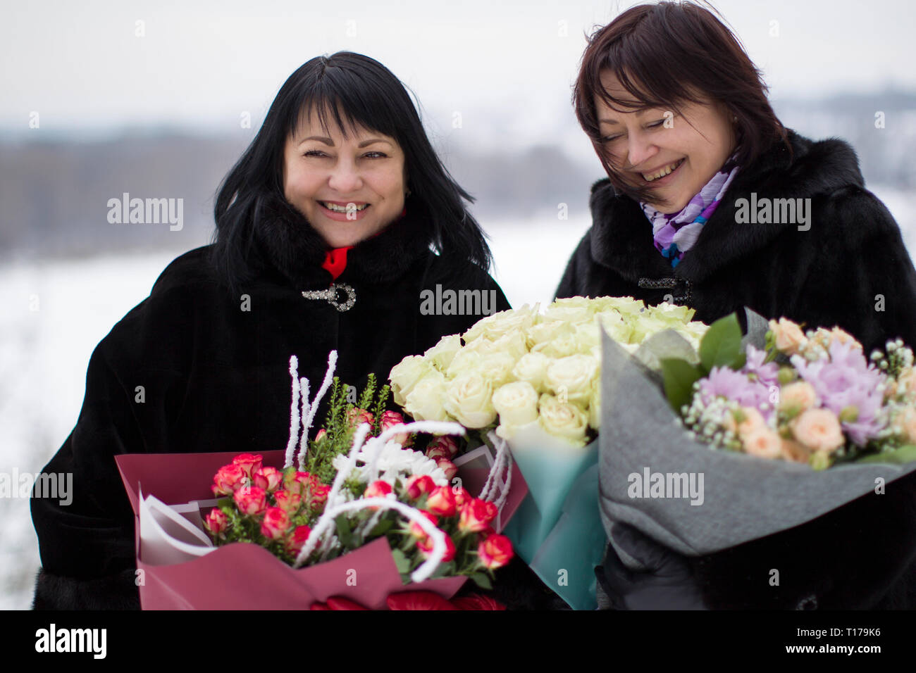 Two mature beautiful women with flowers bouquets.Old friends. Women Friendship. - Stock Image