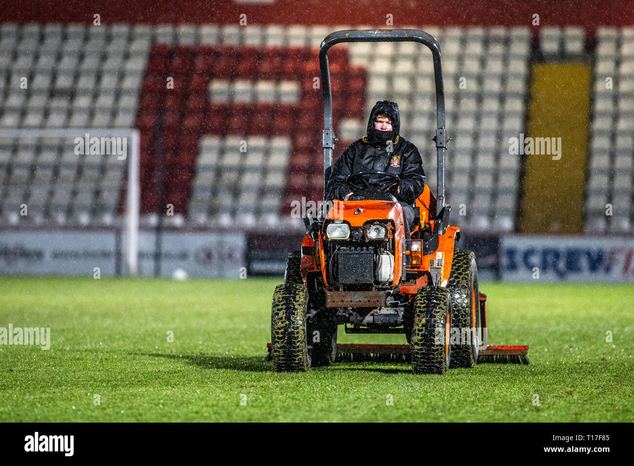 Groundsman maintaining football pitch in rain - Stock Image