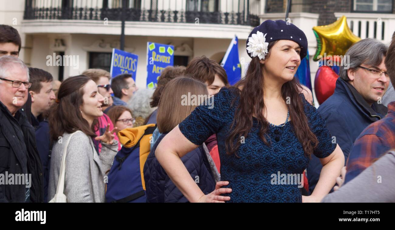 Young woman standing with hands on hips at Remain march in London wearing beret with white flower - Stock Image
