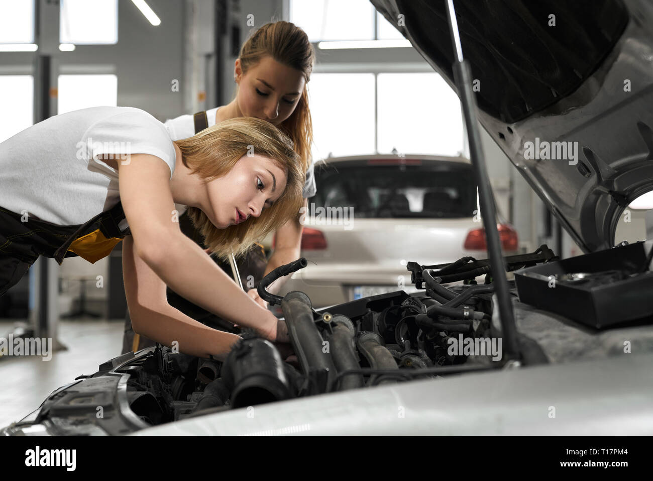 Two mechanics repairing and working maintenance of car in autoservise. Young beautiful blonde girls wearing in coveralls and white t shirts looking at car with opened hood. - Stock Image