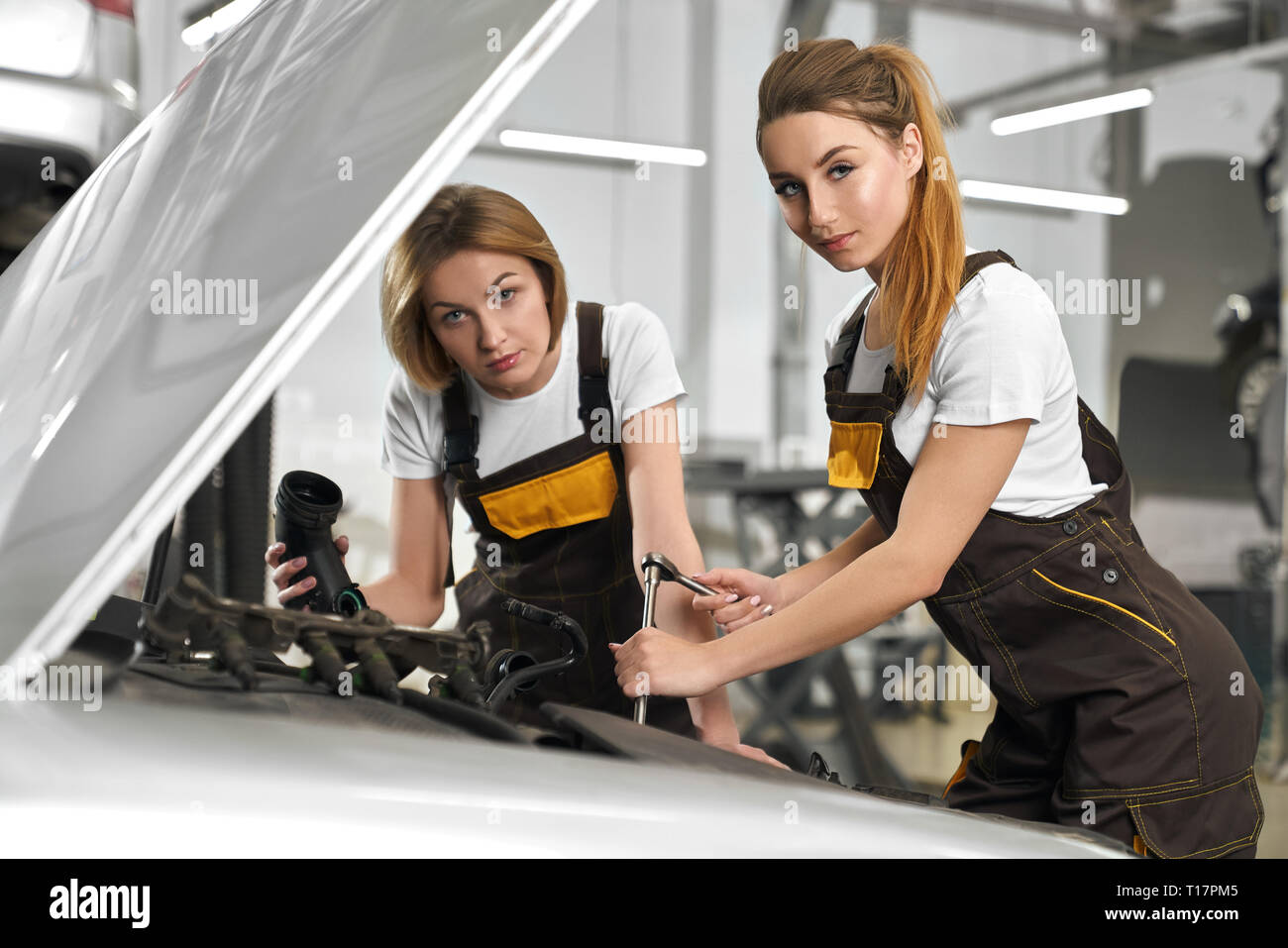 Two pretty female mechanics wearing in coveralls and white t shirt repairing automobile. Beautiful blonde girl holding tools and standing near car with open hood in autoservise. - Stock Image