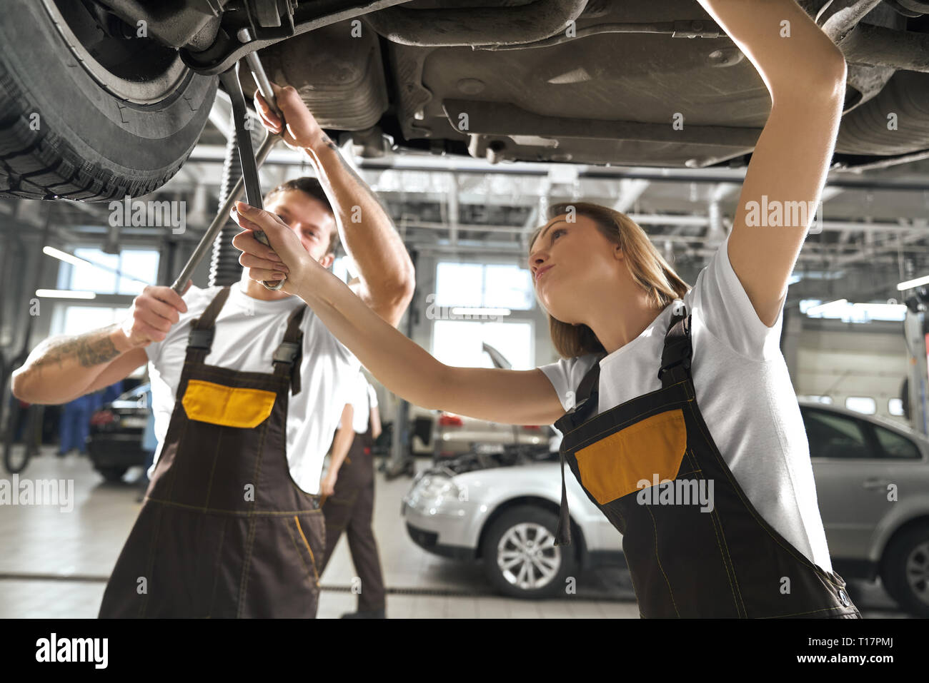 Concentrated young woman and man repairing auto in autoservice station. Professional female and male mechanics holding tools, wrenches and fixing undercarriage of vehicle. - Stock Image