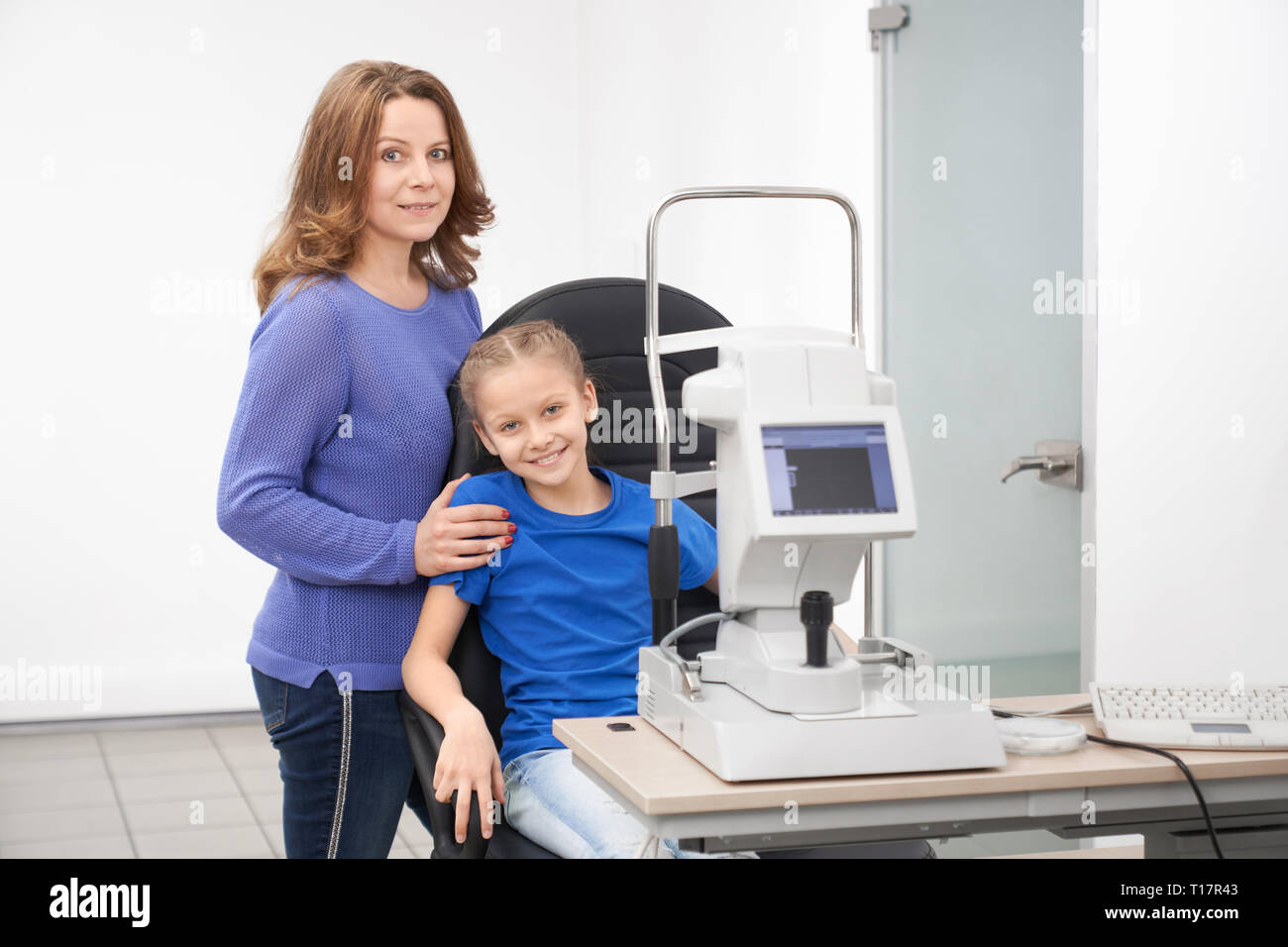 Pretty girl sitting in chair at table with modern slit lamp machine for examining eyesight. Mother and child posing in beautiful new optician office of ophthalmology clinic. Stock Photo
