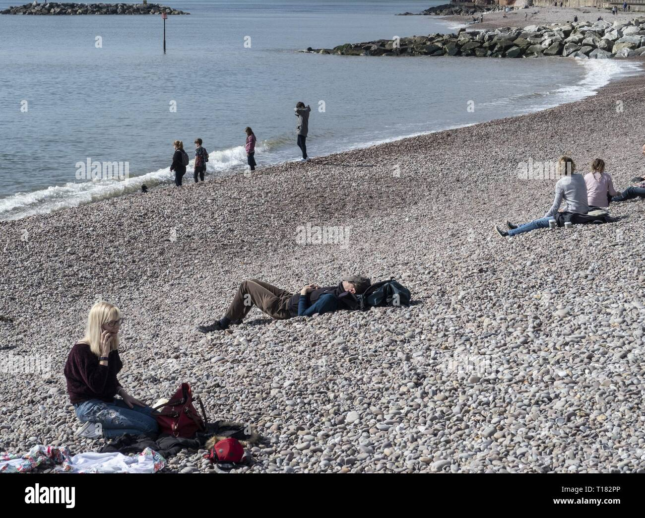 Sidmouth, UK. 24th Mar, 2019. A spot of warm sunshine tempted people onto the beaches at Sidmouth. Credit: Photo Central/Alamy Live News Stock Photo