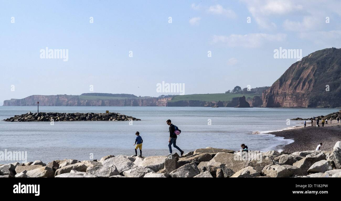 Sidmouth, UK. 24th Mar, 2019. Families playing on the rock groynes atSidmouth. Credit: Photo Central/Alamy Live News Stock Photo