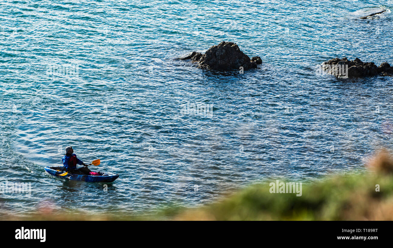 Bray Head, Ireland. 24th March, 2019 Kayaker enjoying calm, warm weather having rest on his passage from Greystones to Bray and looking at cliff's wildlife. Credit: Vitaliy Tuzov/Alamy Live News - Stock Image