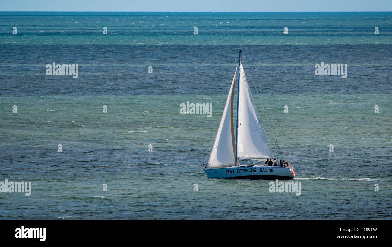 Bray Head, Ireland. 24th March, 2019 Sailing boat making his way in the sea. Credit: Vitaliy Tuzov/Alamy Live News Stock Photo