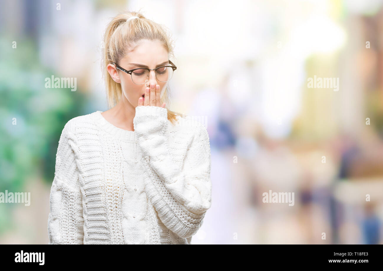 69adc4e80 Young beautiful blonde woman wearing glasses over isolated background bored  yawning tired covering mouth with hand