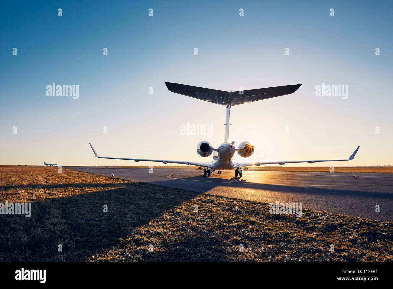 Airport at sunset. Silhouette of private jet against runway. - Stock Image