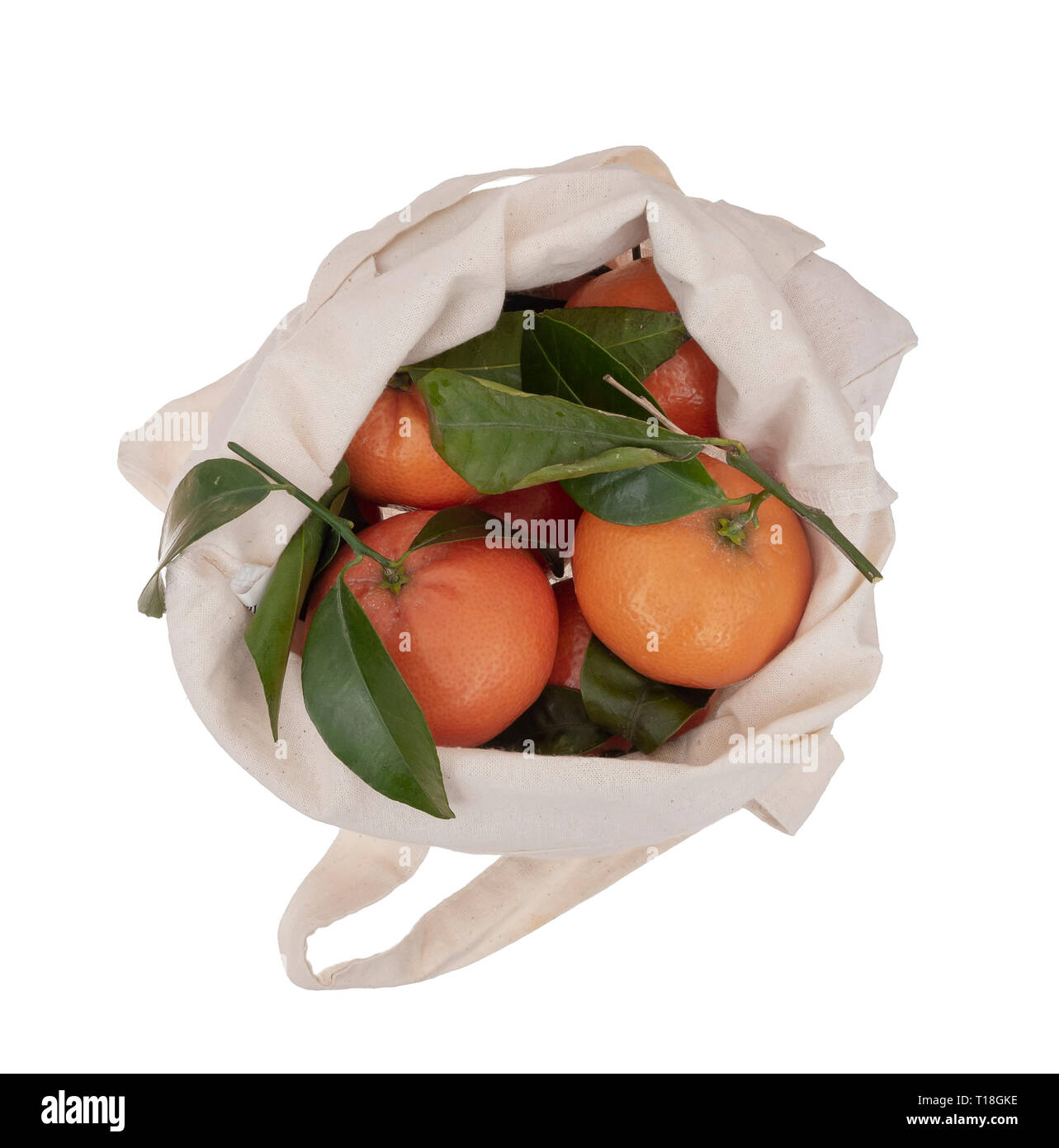 Fresh picked oranges in reusable, recyclable fabric shopping tote bag, isolated on white. For environmentally friendly, green consumers.Overhead view. - Stock Image