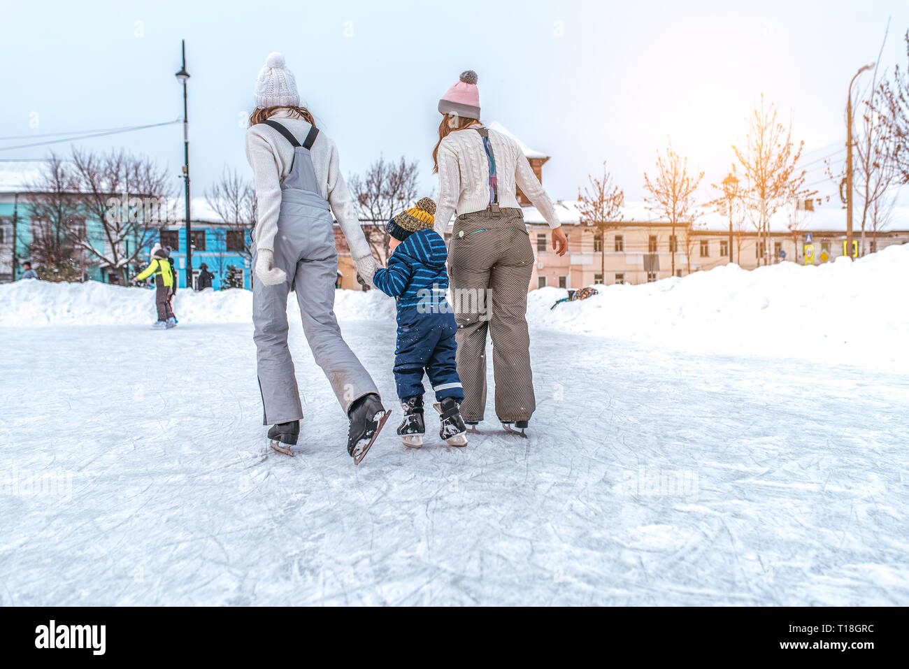 Parents of little boy ride on skating rink, view from rear, girls girlfriend girlfriends, teach son 3-5 years old, ride skating rink winter park. The - Stock Image