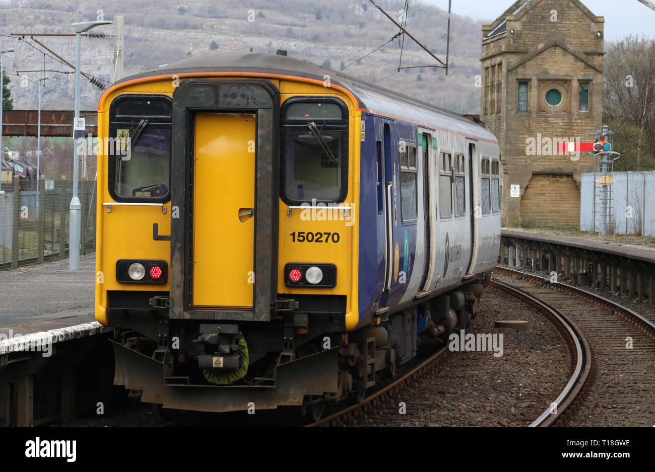 Class 150 sprinter diesel mutiple unit in Northern livery leaving Carnforth railway station with an ordinary passenger service on 21st March 2019. - Stock Image