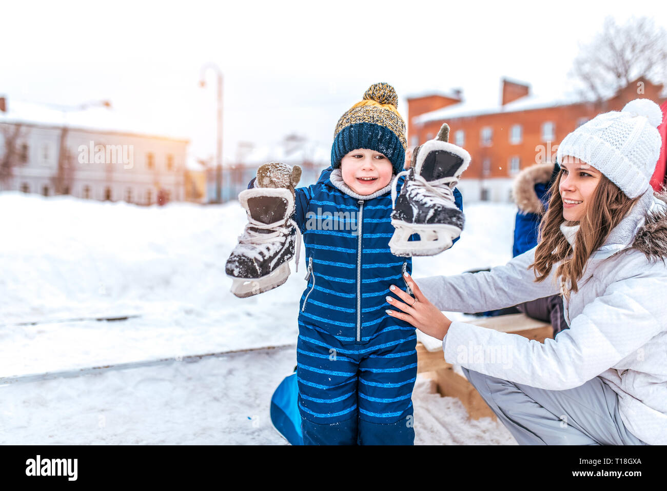 Little son, cheerful joyful boy of 4-6 years old, holds his skates his hands. Mom woman supports him. Caring a change of shoes at winter rink. Rest in - Stock Image