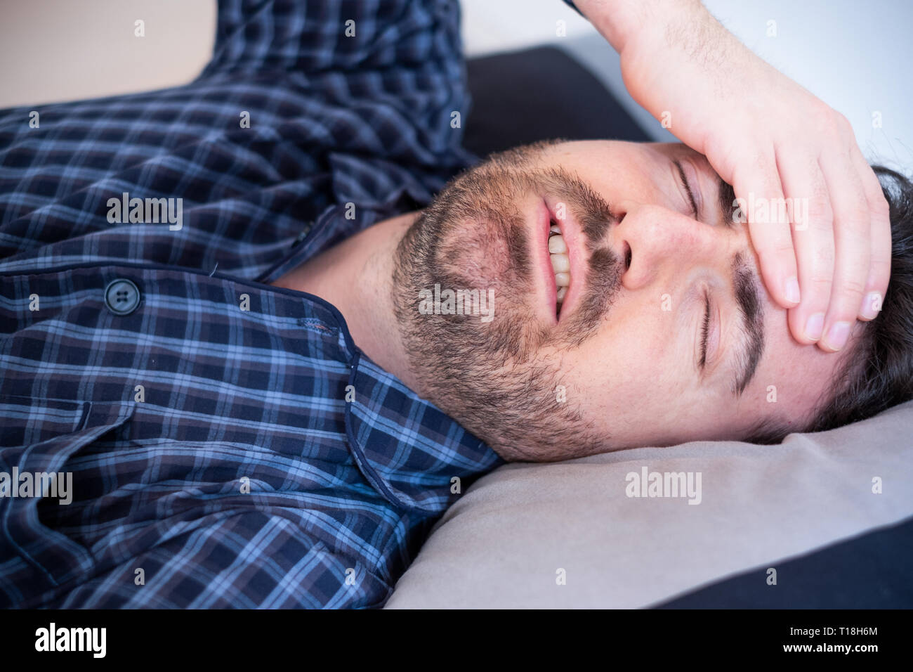 Man with sleep disorder lying in the bed - Stock Image