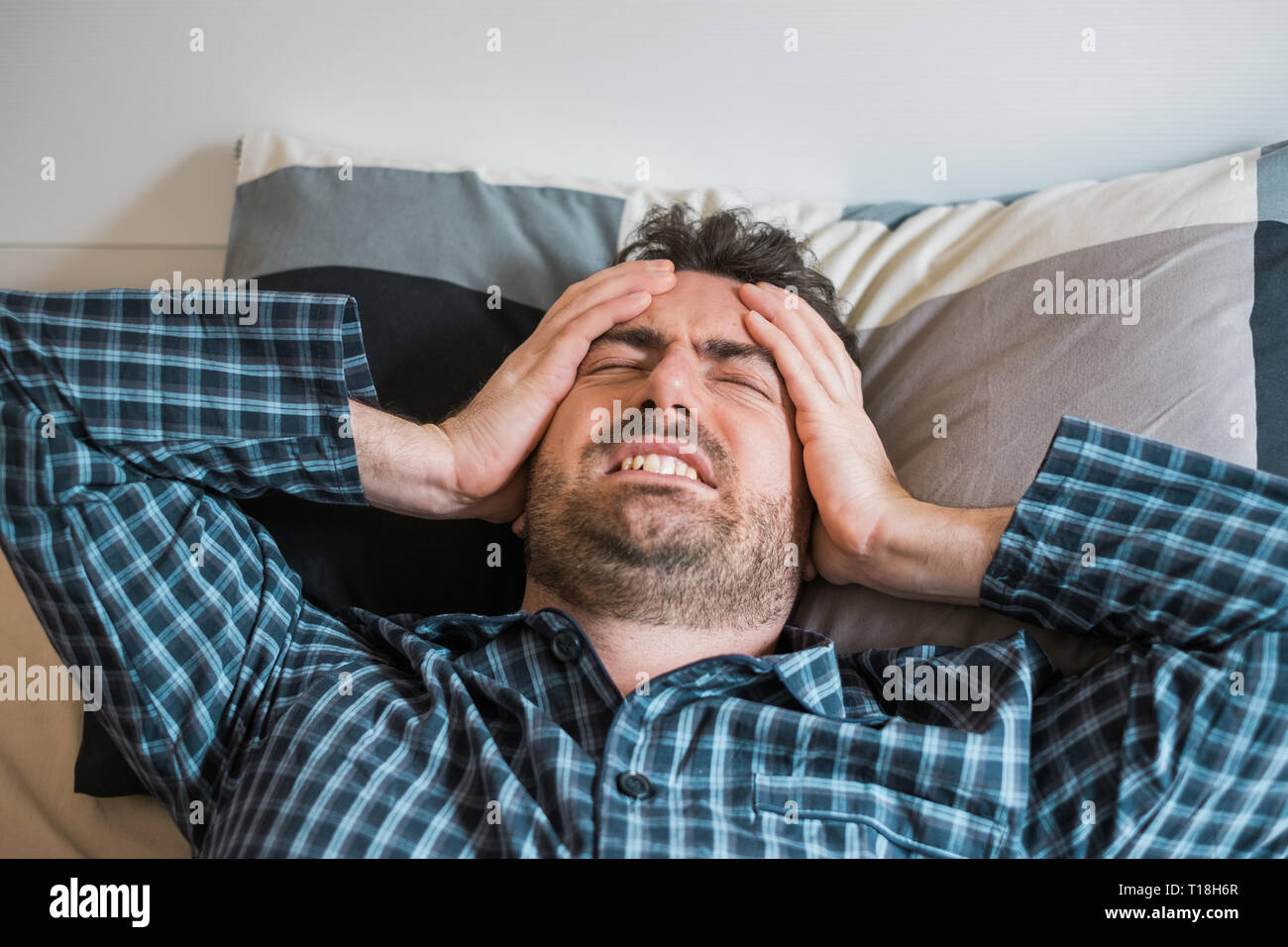 Man with sleep problem in his bed at home - Stock Image