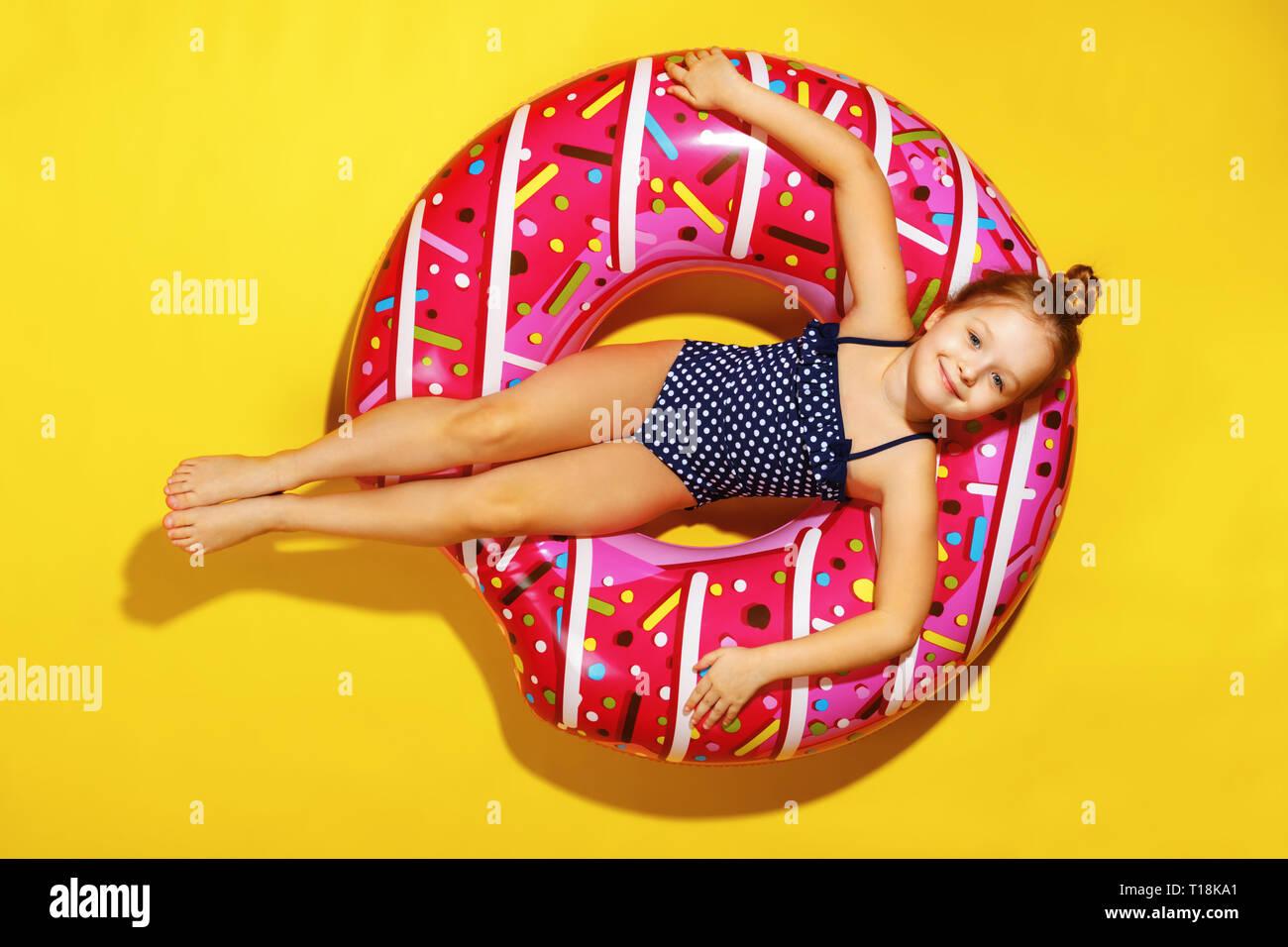 A little child girl in a swimwear suit lying on a donut inflatable circle. Yellow background. Top view. - Stock Image