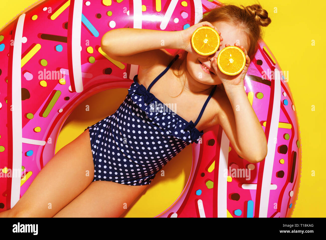 A little child girl in a swimwear suit lying on a donut inflatable circle. Yellow background. Top view. Summer concept. Closeup. - Stock Image
