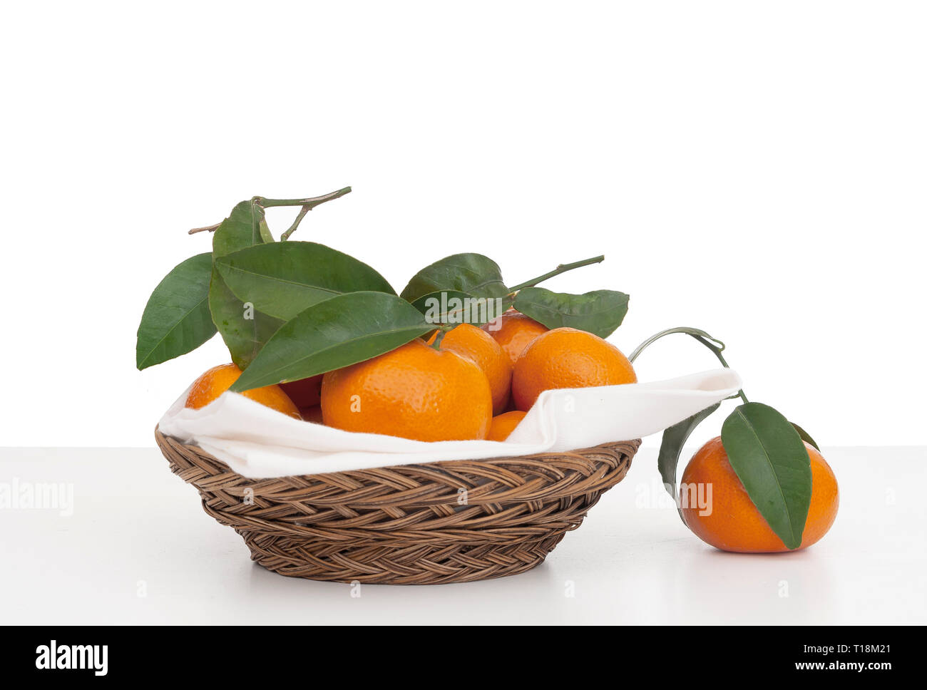 Juicy tangerines, small oranges with leaves in wicker basket with serviette, napkin. Fresh fruit on white, isolated against background. - Stock Image