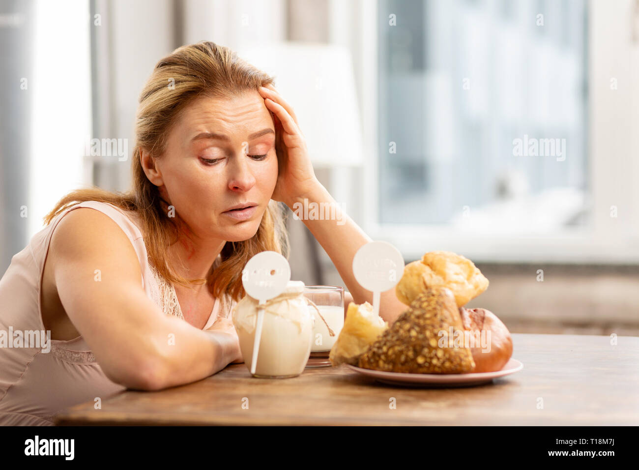 Housewife sitting at the table and looking at foods evoking allergies - Stock Image